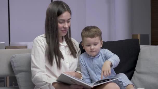 Anya és fia könyvet olvasnak egy kanapén ülve.