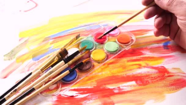 Štětce a akvarel barvy v pohybu na stole
