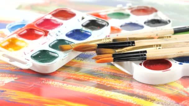 Pinsel und Aquarellfarben in Bewegung auf dem Tisch