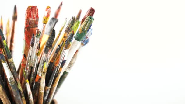 Paint brushes and watercolor paints in motion on the table