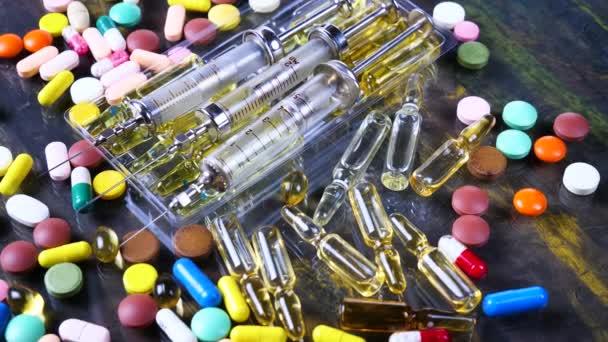 Spritzen und bunte Tabletten rotieren auf dem Tisch