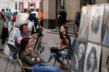 The artist draws a portrait of a girl on the Arbat