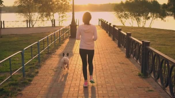 fit female with puppy running at sunset