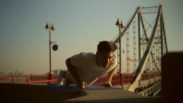 man doing push-ups by the bridge