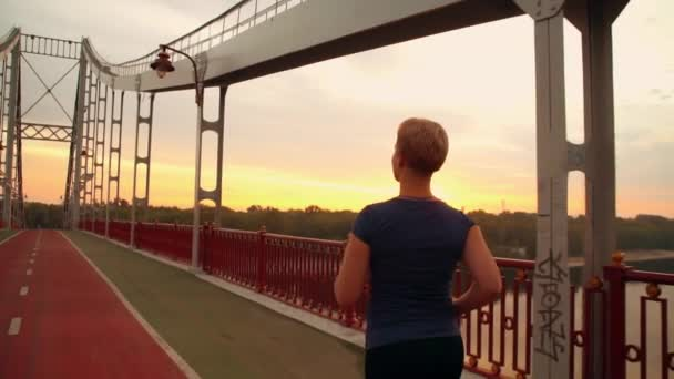 unrecognizable jogger female run on the bridge