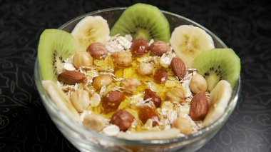 Pouring honey oatmeal with fruit and nuts