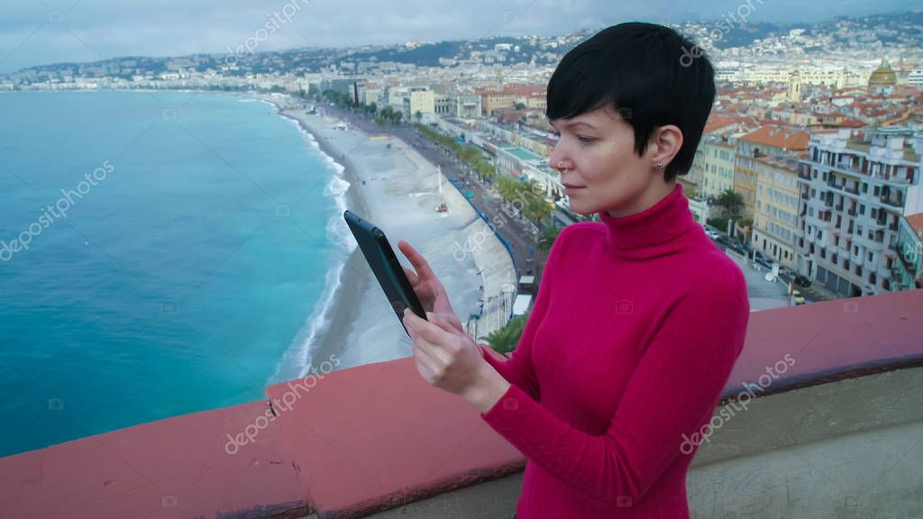 Woman using touch screen tablet in the mediterranean city.