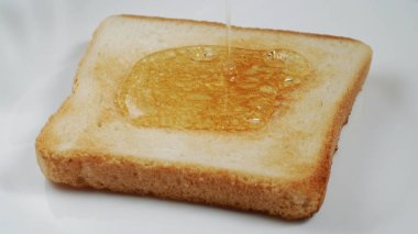 Toast on a plate pour with honey