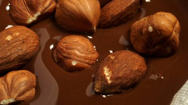 Hazelnuts and almonds fall into the melted chocolate