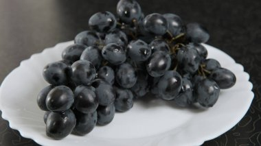 Blue bunch of grapes lying on a platter.