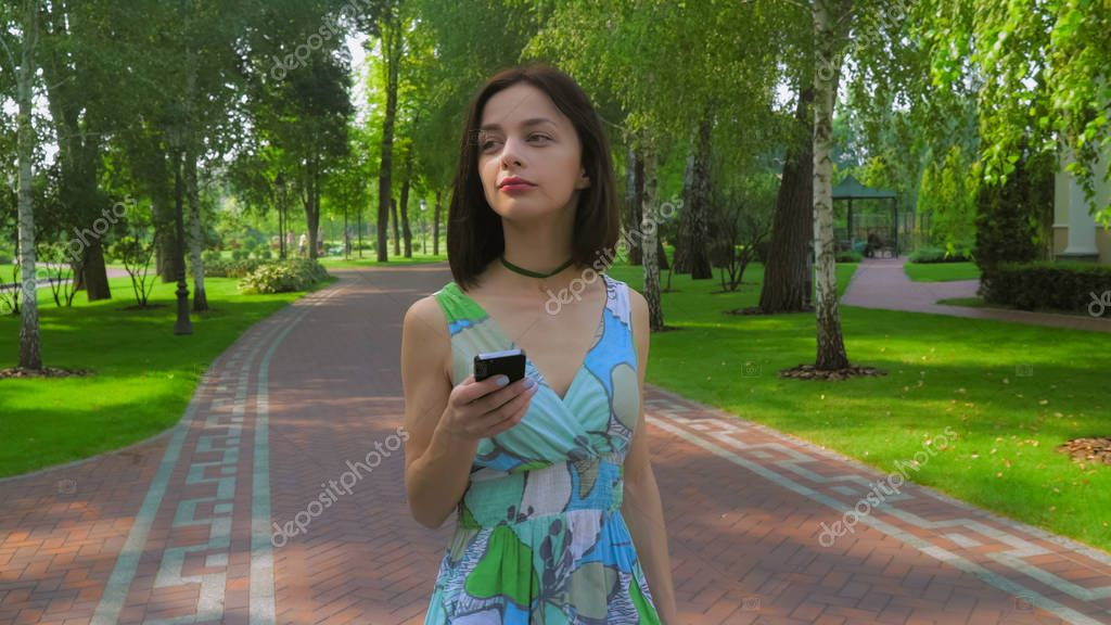 A young girl goes on a path in the park and gaining a message on the phone.
