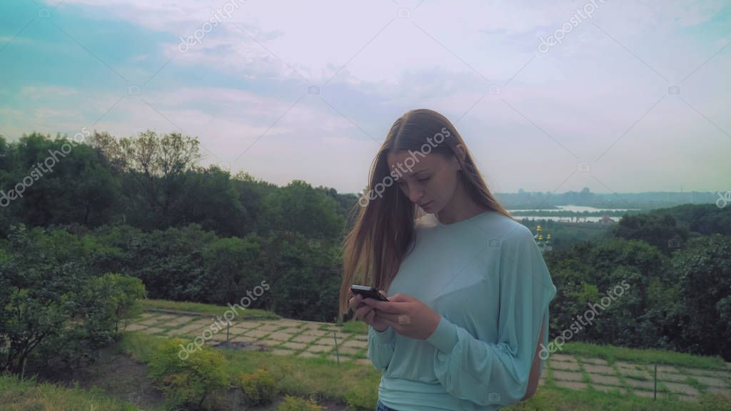 Young stylish girl standing on a hill and gaining a message on the phone.