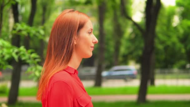 Red haired female walking in green park