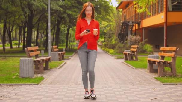 Frau mit langen roten Haaren verwenden mobile Halten Tasse Spaziergänge in der Stadt