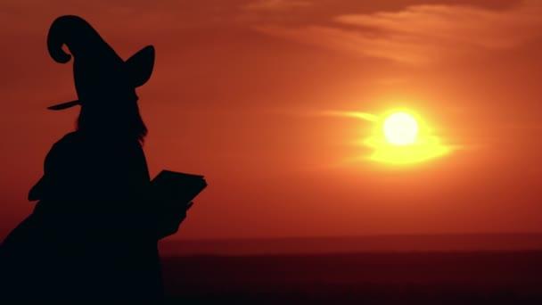 lány jelmez és kalap boszorkány tart könyvet napkelte megtekintéséhez