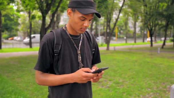 portrait young man holding mobile chatting online outdoors