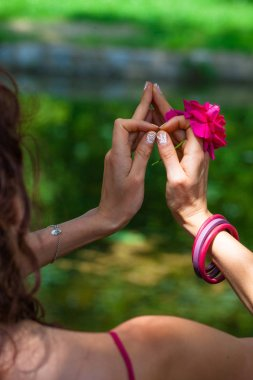 woman hands with flower in yoga mudra gesture outdoor in nature in front lake back view