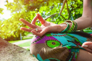 closeup of woman hand in mudra gesture practice yoga sit on tree summer day