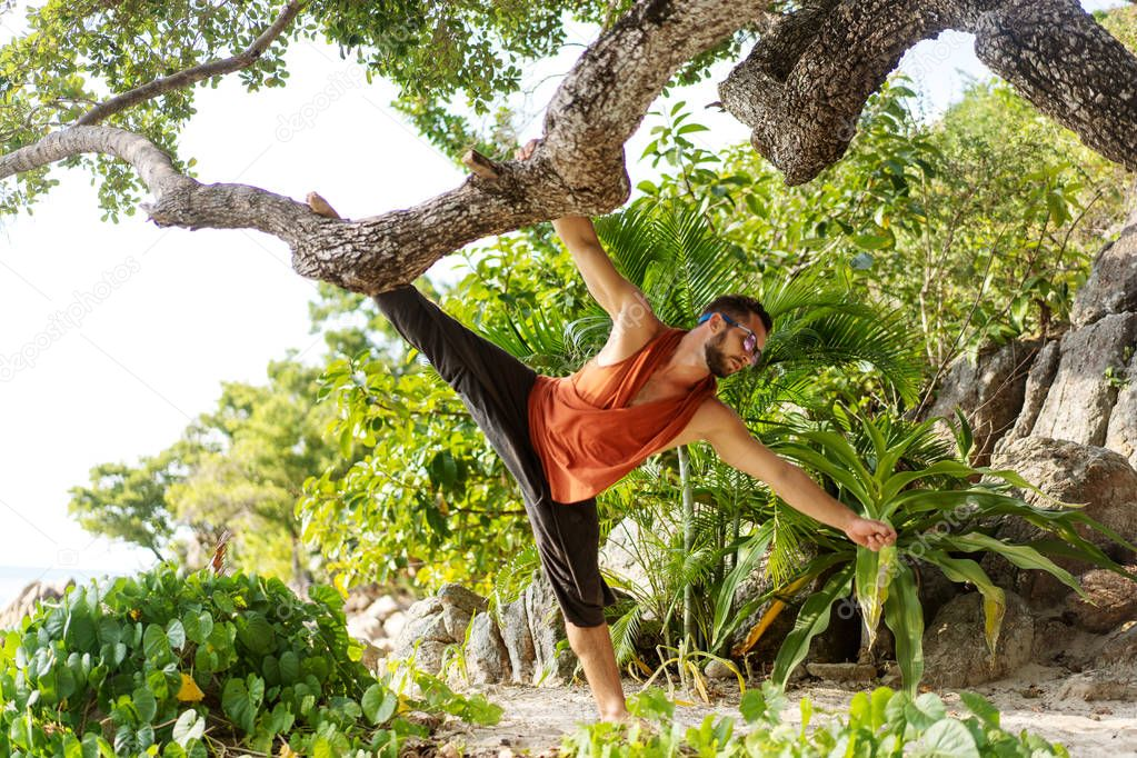 fashion guy in tropical palms doing acrobatics