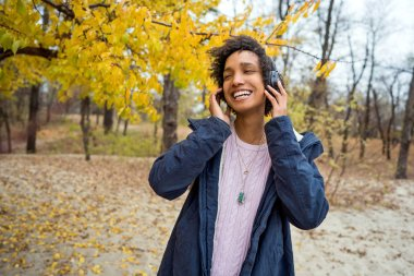 beautiful african girl in autumn park listening to music outdoors smiling