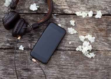 phone with headphones lie on a wooden background