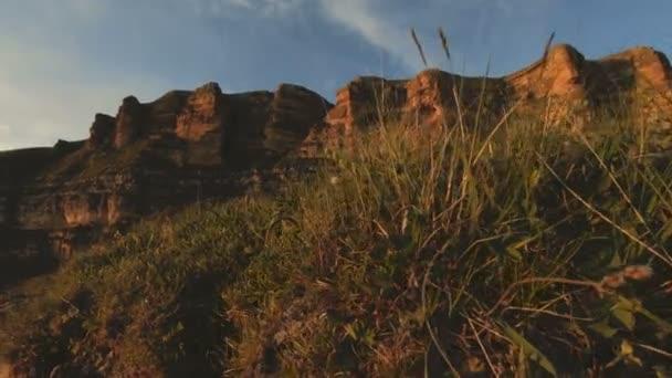 Mountain sunset over the peak rock. Dark key sunset light in the mountains parallax rocks rock grass