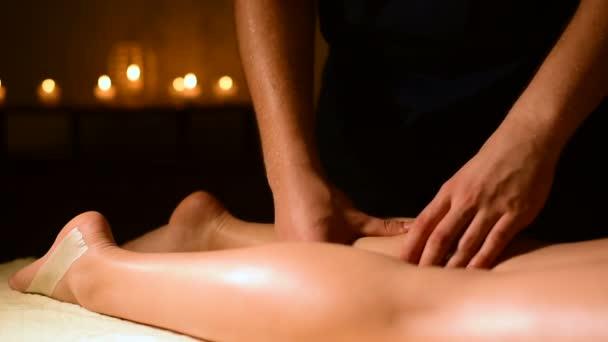 Masáž s olejem na pozadí svíčky v temné místnosti spodní části ženské nohy