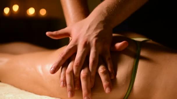 Masér v temné místnosti dělá hip masáž s olejem pro ženy. Lázeňské procedury masáž ženy