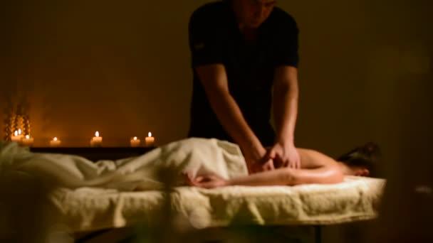 Detail spa masáž Zenske ramena a zpět. Mužské ruce masážní ženě v temné místnosti se svíčkami na pozadí
