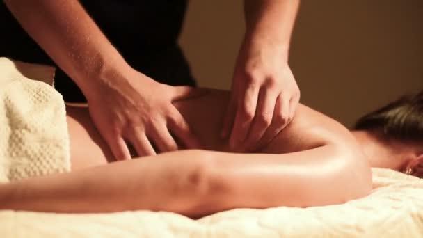 Detail mužské ruce dělá léčení masáž s olejem mladé dívce v kanceláři tmavé kosmetologie. Tmavě klíč