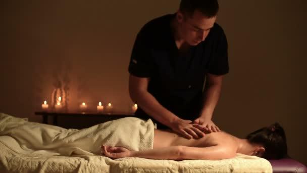 Medium Shot Ein großer Kerl Ein Masseur massiert ein junges Mädchen, das mit dem Gesicht nach unten auf einer Couch in einem dunklen Büro liegt, mit Kerzen im Hintergrund