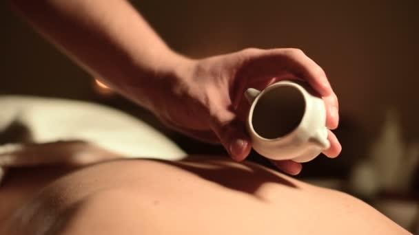 Nahaufnahme männlicher Hände in einem geretteten Salon vor einer Massage. Massageöl in einem dunklen Raum auf dem Hintergrund brennender Kerzen wird auf die Haut der Mädchen gegossen