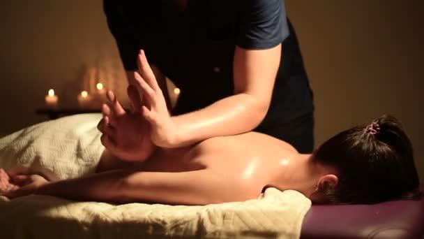 Muž dělá masáž k mladé ženě s loktem. Tmavě klíč. Detailní záběr záběr
