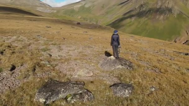 Aerial view of a girl photographer walking on a plateau in the mountains with his camera on the background of rocks and mountains. Hobbies in nature 4k