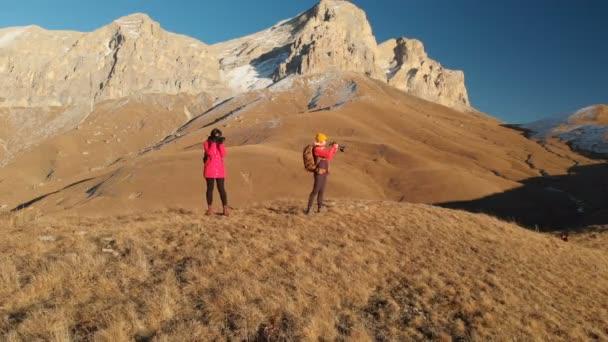 Luftaufnahme von zwei Reisen Mädchen mit Rucksäcken und Kameras schlendern Sie durch die Hügel zwischen epischen Felsen in den Bergen. Mädchen-Fotografen fotografieren mit ihren Kameras bei Sonnenuntergang
