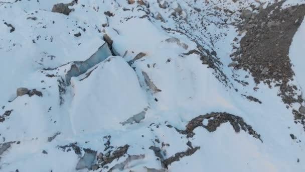 Luftbild Nahaufnahmen Kante von einem fließenden Gletscher bedeckt mit Schnee und Steinen, die hoch in den Bergen. Natürliche Vernichtung von schmelzenden Gletschern und globale Erwärmung