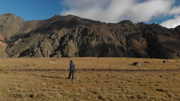 Aerial view of a girl photographer walking on a plateau in the mountains with his camera on the background of rocks and mountains. Hobbies in nature 4k.