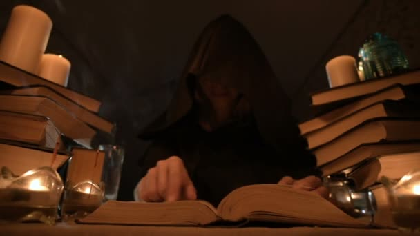 Medium close-up girl magician in a hood in a dark room by candlelight and looking for a spell turning over a book. Low key. Mystic Small DOF