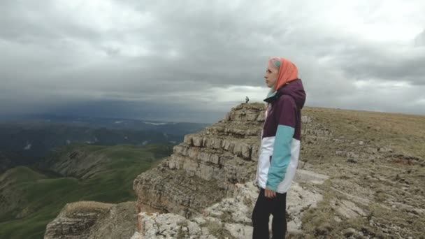 The girl walks in nature on a plateau next to a high cliff. Travel concept