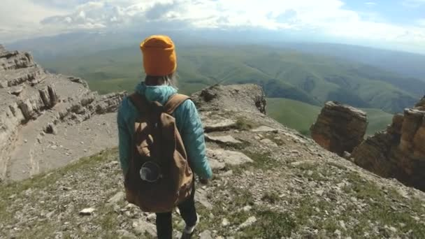 A girl with a backpack walks in nature on a plateau near a high precipice. Travel concept