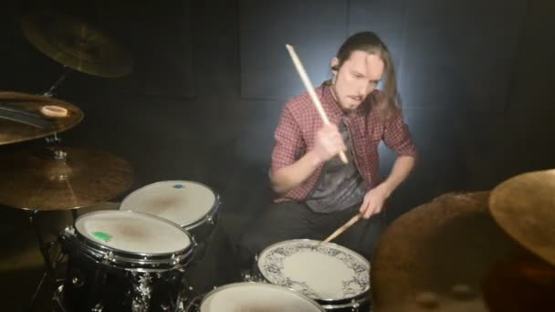 A long-haired drummer starts playing a drum kit in a dark room against a black background. Rock musician. Static plan. Wide angle