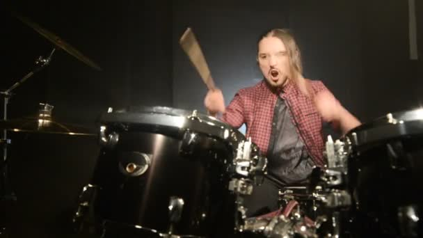 Long-haired drummers play drum kit in a dark room on a black background. Rock musician. Static plan. Wide angle