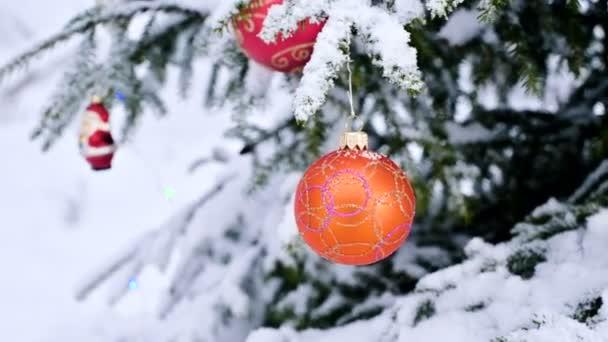 Közelkép a karácsonyi játék egy hóval borított élénk fa a háttérben fény a téli erdőben. Kis Dof