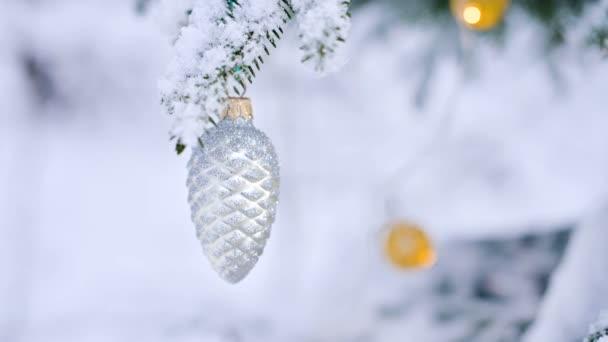 Nahaufnahme eines Weihnachtsspielzeugs auf einem schneebedeckten lebendigen Baum im Winterwald vor dem Hintergrund von Lichtern. kleine dof