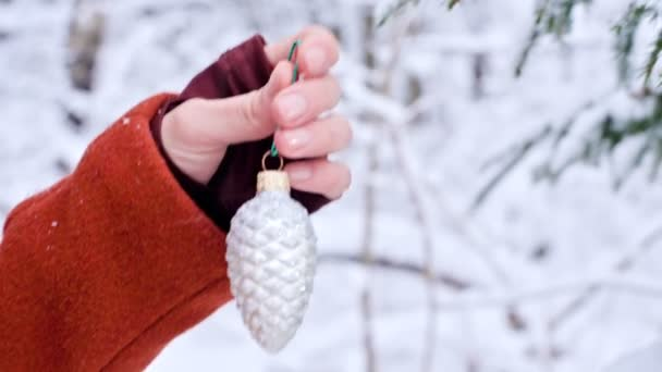 close-up female hands in mittens hands hang Christmas toys decoration tree in a real winter from a snow-covered branch of a New Year tree.