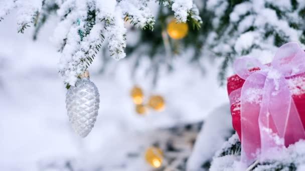 Közeli vörös Szilveszter ajándék, karácsonyi játékok, az ágak egy havas karácsonyi fa a téli erdő melletti fehér szalaggal. A karácsonyi ajándékok és az új év