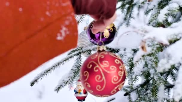 zblízka ženské ruce palčáky rukou pověsit vánoční strom dekorace hračky v skutečné zimě od zasněženou větev stromu nový rok