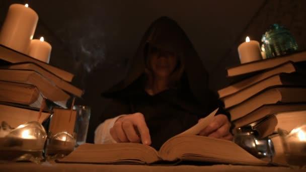Střední detail dívka kouzelník v kapuci v temné místnosti při svíčkách a hledají kouzlo soustružení nad knihou. Nízký klíč. Mystic malé Dof