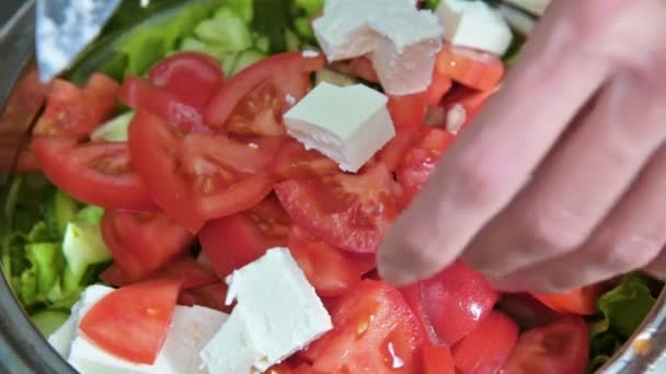 Zblízka se žena kuchař ruky dávat Kostičky sýra Feta na Řecká Veganská rajčatový salát s olivami a listy salátu. Pojem zdravé výživy a životního stylu