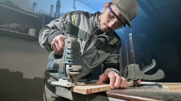 Mladý muž s bradkou v šedé kombinézu a brýle povoláním tesař funguje jako elektrická skládačka ve své domácí dílně. Řezání dřevěných dílů